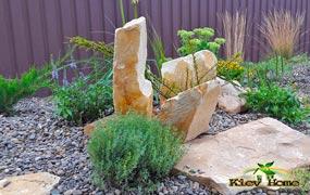 Декорирование валунами песчаника клумбы с растениями