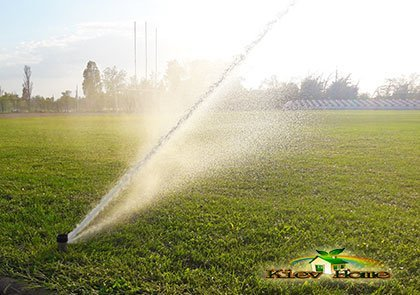 Роторный дождеватель поливает футбольное поле